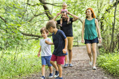 Happy young family walking outside in green nature Stock Image