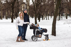 Happy young family walking in the park in winter Stock Photography