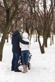Happy young family walking in the park in winter Royalty Free Stock Image