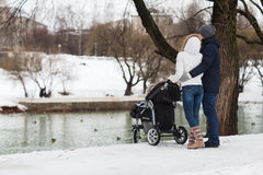 Happy young family walking in the park in winter Royalty Free Stock Photos
