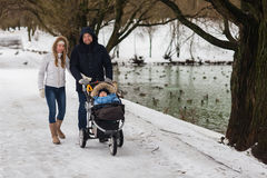 Happy young family walking in the park in winter Stock Image