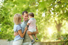 Happy young family walking in summer park. Stock Photos