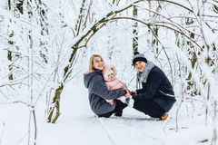 happy young family walks with baby on winter street, mom, dad, c royalty free stock photo