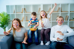 Happy young family watching television. On sofa Stock Photos