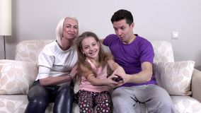 Happy young family watching television together stock video