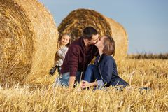 Happy young family with 2 year old girl next to hay bales Stock Images