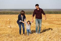 Happy young family with 2 year old girl walking in a harvested f Royalty Free Stock Images