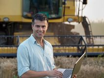 Engineer with laptop and combine harvester Stock Photo
