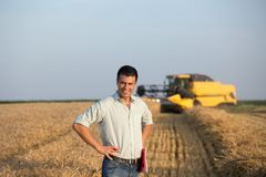 Engineer with notebook and combine harvester in field Stock Image