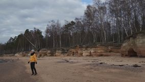 Happy young fashion addicted woman doing sports on the beach in cold Spring weather - Veczemju Klintis, Latvia - April. Happy young fashion addicted woman doing stock video footage