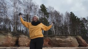 Happy young fashion addicted woman doing sports on the beach in cold Spring weather - Veczemju Klintis, Latvia - April. Happy young fashion addicted woman doing stock footage