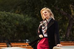 Happy young fashion blond woman walking in autumn park stock image