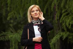 Happy young fashion blond woman walking in city park stock photography