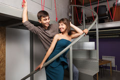 Happy young fashion couple flirting in office Stock Images