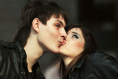 Happy young fashion couple kissing outdoor Stock Photos