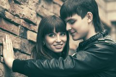 Happy young fashion couple in leather jackets at the brick wall Royalty Free Stock Images