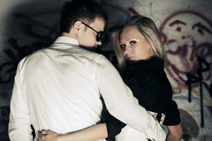 Happy young fashion couple in love at the grungy wall Royalty Free Stock Photography