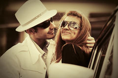 Happy young fashion couple in love next to vintage car Royalty Free Stock Photography