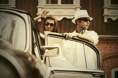 Happy young fashion couple in love next to vintage car Royalty Free Stock Photo