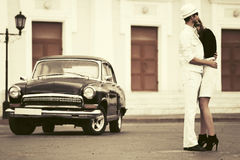 Happy young fashion couple in love next to vintage car Royalty Free Stock Photos