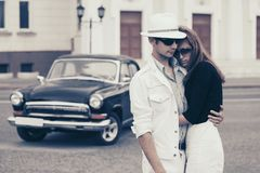 Happy young fashion couple in love next to vintage car stock photo