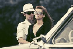 Happy young fashion couple next to vintage car royalty free stock image