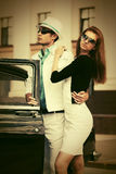 Happy young fashion couple next to vintage car Royalty Free Stock Photos