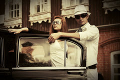 Happy young fashion couple next to vintage car Stock Images