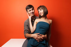 Happy young fashion couple sitting on the desk Royalty Free Stock Photos