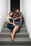 Happy young fashion couple sitting on the steps in office Stock Photos