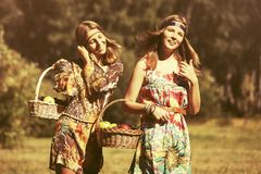 Happy young fashion girls with a fruit basket walking outdoor Royalty Free Stock Images