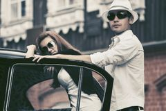 Happy young fashion hipster couple next to vintage car stock photography