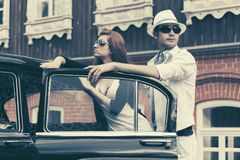 Happy young fashion hipster couple next to vintage car royalty free stock photos