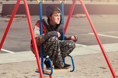 Young fashion hipster man sitting on the swing. Happy young fashion hipster man sitting on the swing Royalty Free Stock Image