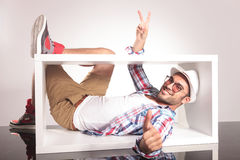 Happy young fashion man lying inside of a white box Royalty Free Stock Photo