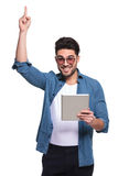 Happy young fashion man pointing up. While holding a computer tablet in his left hand Stock Images
