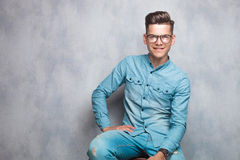 Happy young fashion man sitting Stock Image