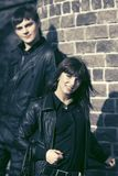 Happy young fashion couple in leather jackets at the brick wall. Happy young fashion men and women wearing black leather jackets at the brick wall Stock Image
