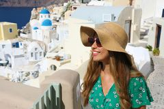 Happy young fashion model in Santorini. Beautiful tanned woman with sunglasses enjoying Oia small town in Santorini touristic royalty free stock images