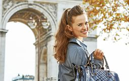 Happy young fashion-monger in trench coat in Paris, France. Stylish autumn in Paris. Portrait of happy young fashion-monger in trench coat in Paris, France Stock Photos