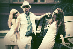 Happy young fashion people next to retro car Royalty Free Stock Photography