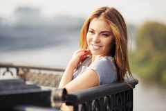 Happy young fashion woman at the cast iron fence Royalty Free Stock Image