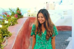 Happy young fashion woman with green dress walking in Oia village, Santorini. Female travel tourist on her summer vacations in Gr stock image