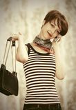 Happy young fashion woman with handbag calling on cell phone Royalty Free Stock Photography