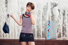 Happy young fashion woman with handbag calling on mobile phone Stock Images