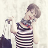 Happy young fashion woman with handbag calling on mobile phone Royalty Free Stock Photo