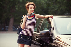 Happy young fashion woman with handbag next to her car Stock Images