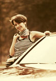 Happy young fashion woman with handbag next to her car Royalty Free Stock Image