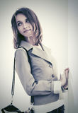 Happy young fashion woman with handbag standing at the wall Royalty Free Stock Photography