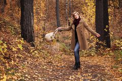 Happy young fashion woman with handbag walking in autumn park royalty free stock photography